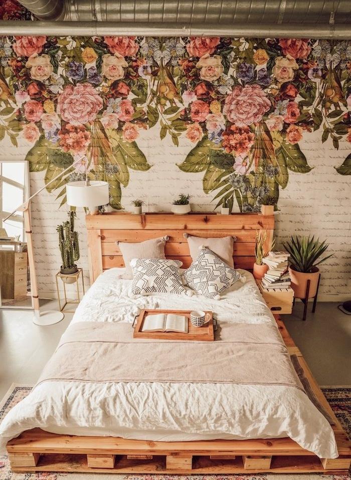 lit en palette avec tete de lit bois diy, mur décoré de dessin imprimé floral sur briques blanches, pots de plantes vertes en guise de chevet