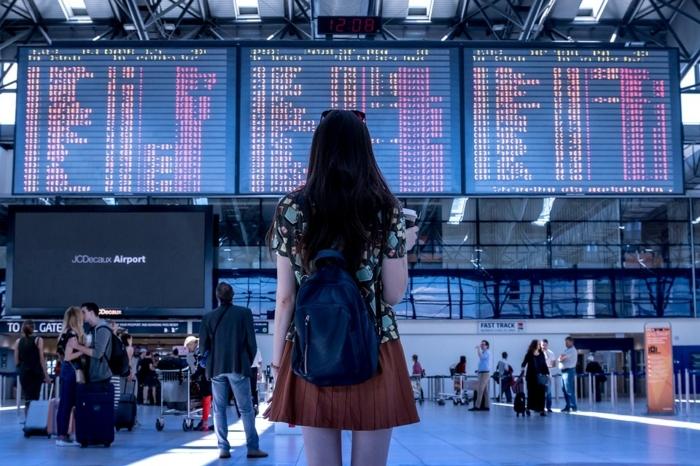 jeune fille devant le tableau d aéroport, grande salle d attente, aéroport, sac à dos, jupe couleur terracotta
