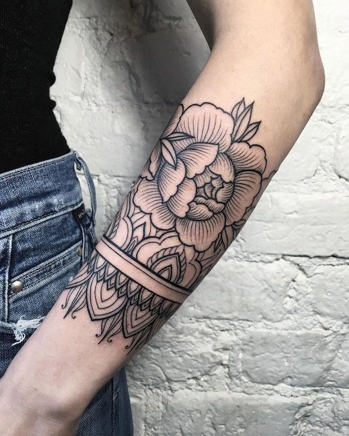 tatouage bras, motif pivoine, mur en briques blanches, jeans bleus, top noir, tatouage fleur et mandala