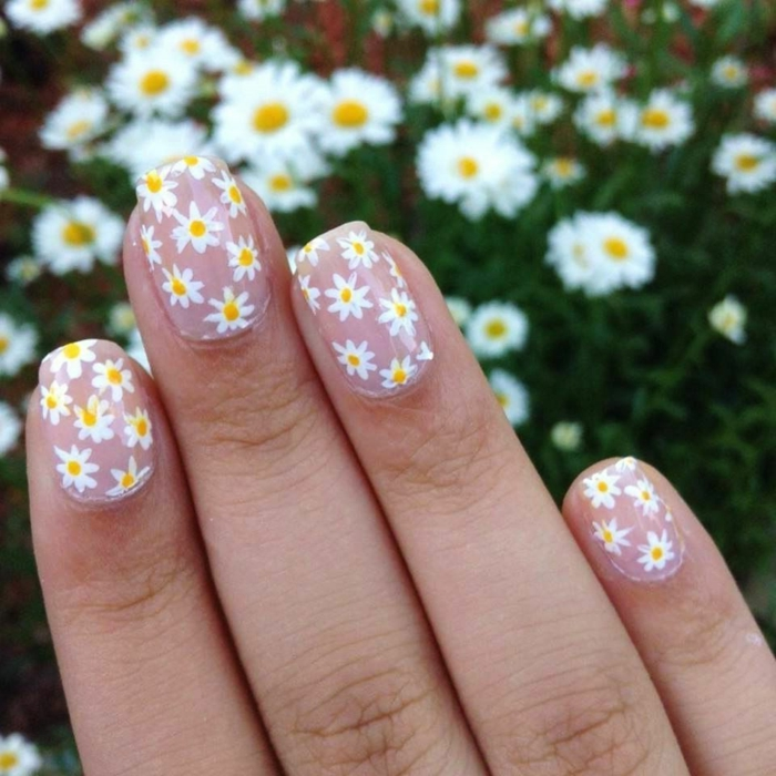 ongles nail art paquerettes, manucure féminine avec fleurs en rouge et blanc sur un fond rose clair