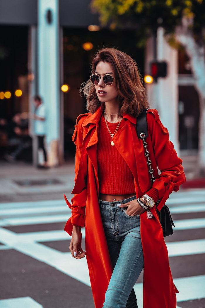 Jean classique et top chemise rouge courte associés à un manteau rouge classe, lunettes de soleil rondes, bijoux modernes