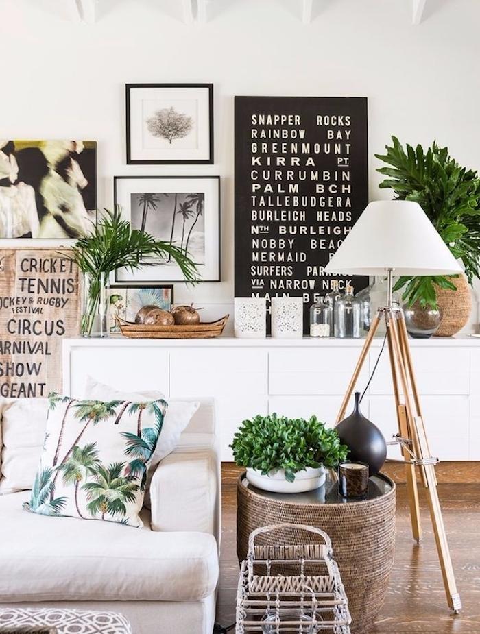 table de service tressée, canapé blanc cassé, coussin imprimé palmier, meuble salon blanc, mur de cadres sur fond blanc, accents deco exotique
