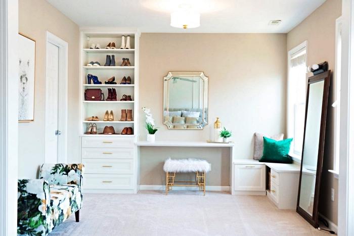 armoire a chaussure semi-ouvert à côté de la coiffeuse dans une chambre à coucher en blanc, or et vert émeraude