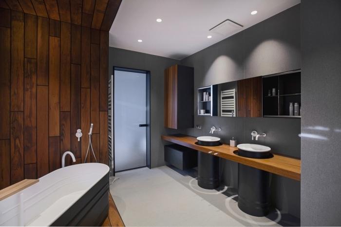 modèle de salle de bain grise au plafond et sol blancs avec revêtement mural à effet bois, modèle de baignoire autoportante blanc et bois