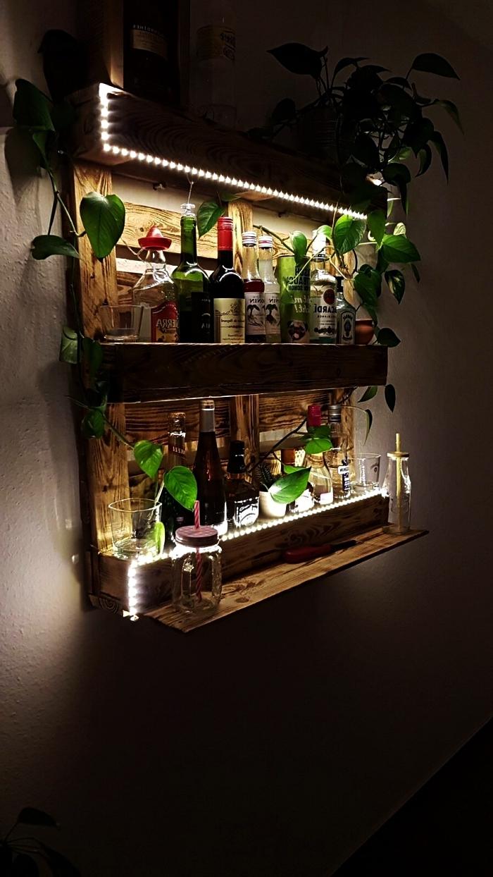 meuble de bar mural en palette pour ranger ses bouteilles d'alcool, deco palette de plantes vertes et d'une guirlande à led