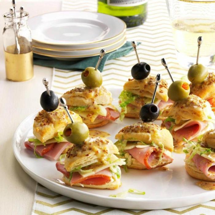 mini sandwiches avec jambon, brochettes au jambon et au fromage, olives, assiette blanche, brochette apéro