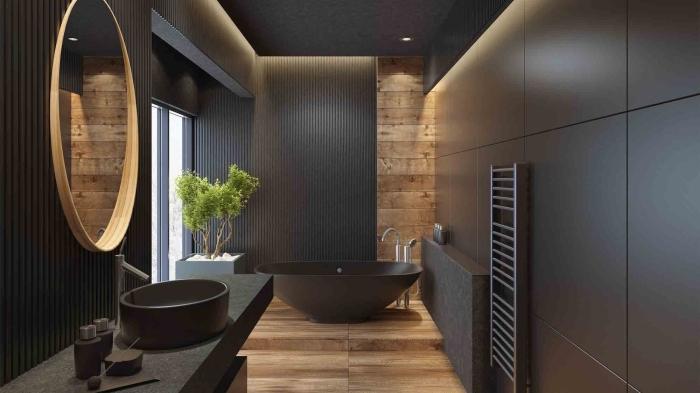 décoration de salle de bain noire aux murs noirs avec plancher imitation planches de bois, modèle de baignoire autoportante en noir mate