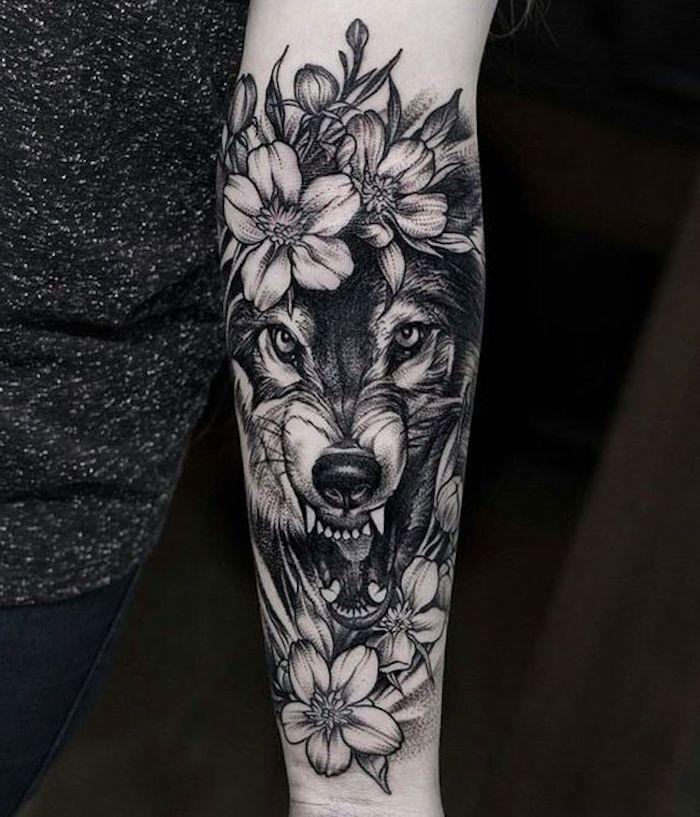 modele de tatouage loup sinistre, fleur de cerisier, tatouage encre noire, tatouage femme avant bras