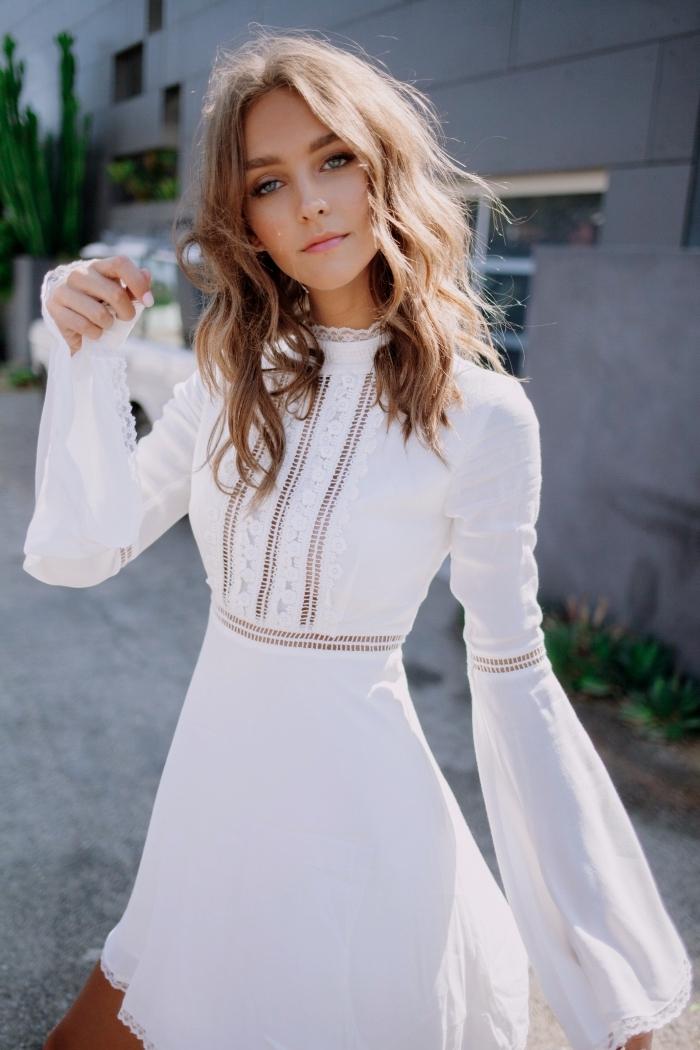 modèle de robe blanche courte aux manches à effet avec top col montant à détails broderie, coiffure cheveux wavy