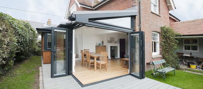 extensuin pour salle à manger en prolongement d un salon avec des portes battantes sur terrasse bois