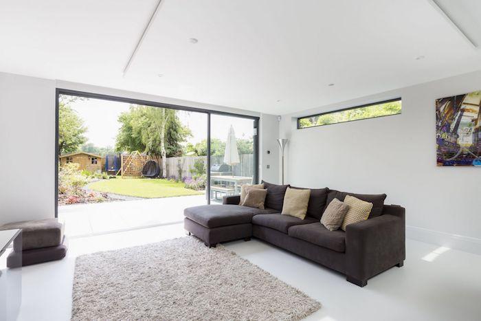 murs blancs et style minimaliste d amengemeent extension garage avec tapis gris clair et canapé gris foncé