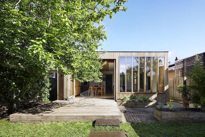 agrandissement bois abritant petit studio avec cuisine ouverte sur salle à manger et salon, sur terrasse en bois