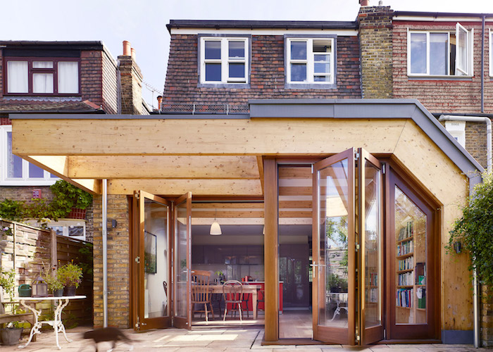 idee d amenagement agrandissement bois avec cuisine grise avec ilot central rouge ouverte sur salle à manger bois et coin repos à grande bibliotheque