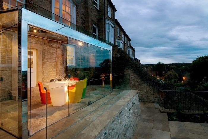 extension vitrée avec une table à éclairage LED entourée de fauteuils dépareillées sur terrasse exterieure