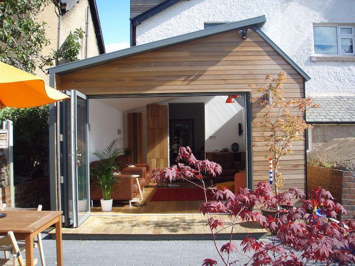 agrandissement bois pour votre salon décoré de canapés marrin, tapis rouge et fauteuil rouge sur parquet bois clair