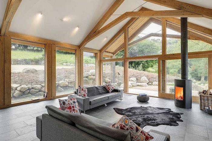 extension ossature bois et portes vitrées à encadrement de bois dans un salon à canapés gris, cheminée moderne design minimaliste