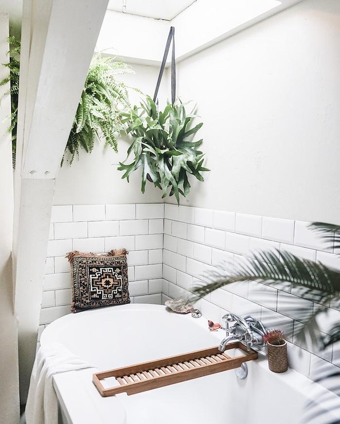 salle de bain zen esprit deco jungle avec des plantes vertes en pot suspendus, baignoire blanche, soubassement carrelage blanc, coussin décoratifs oriental