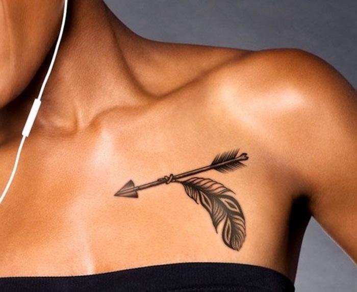 tatouage élégant en noir, flèche et plume, symboles indiens tatoués sous la clavicule de jeune femme