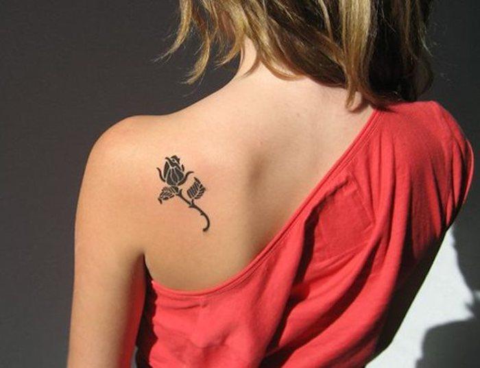 tatouage rose minimaliste, tatouage dos femme, top rouge, fleur de rose avec deux feuilles encre noire