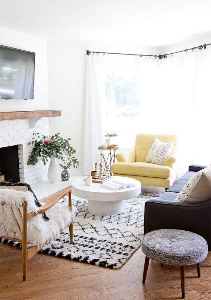 Fauteuil jaune dans un salon avec peinture murale blanche, tapis shaggy noir et blanc, table basse ronde scandinave déco avec motifs ethnique chic