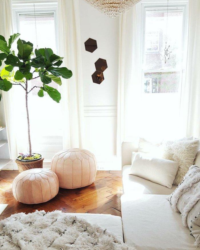 Plante verte haute près de deux poufs marocains, canapé en angle blanche, déco scandinave simple