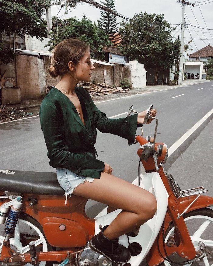 Femme en moto rouge et blanc, tenue décontractée femme, look casual à la mode, jean courte déchiré et chemise verte manche evasee