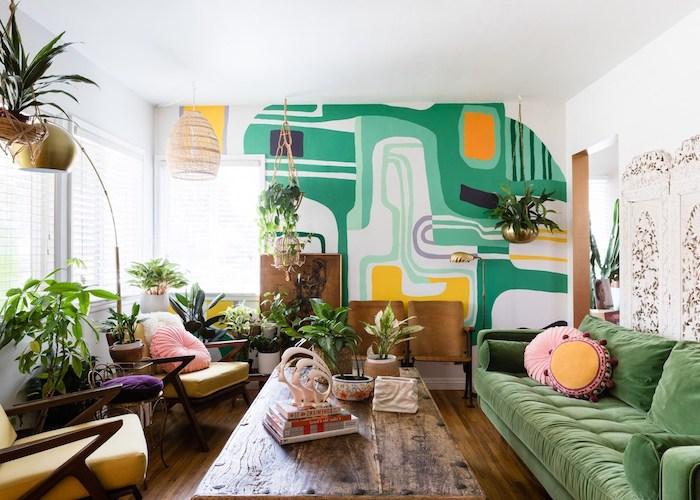 canapé vert, table basse bois brut, fauteuils jaunes, mur d accent repeint de motif géométriques, plantes vertes