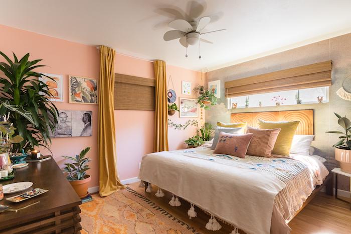 mur d accent rose, idee de mur de cadres, linge de lit coloré, tapis oriental, commode bois, deco tropicale à accents exotiques et végétation