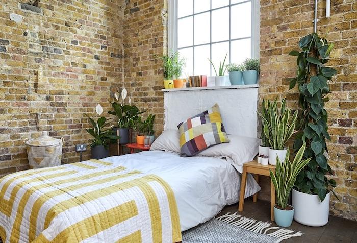 deco chambre industrielle aux murs de briques, linge de lit coloré, petites et grandes plantes en pot, carrelage gris foncé, tapis noir et blanc, petits pots sur rebord de fenetre