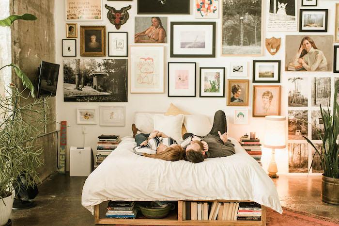 comment decorer une chambre cocooning boheme chic avec grand mur de cadres, lit en palette avec rangements livre intégrés, sol beton gris, plantes en pots autour