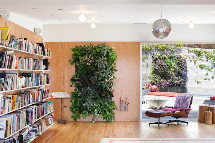 mur végétal intérieur sur un panneau de bois, bibliothèque originale, fauteuil et fauteuil de pied cuir