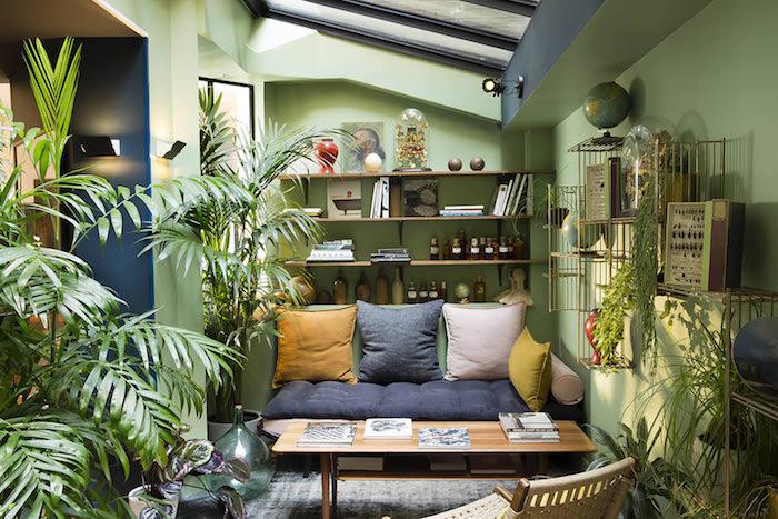 mur couelur vert, table bois et canapé gris et vert, coussin gris, blanc et jaune, multitude de vegetaux en pots par sol, deco tropicale