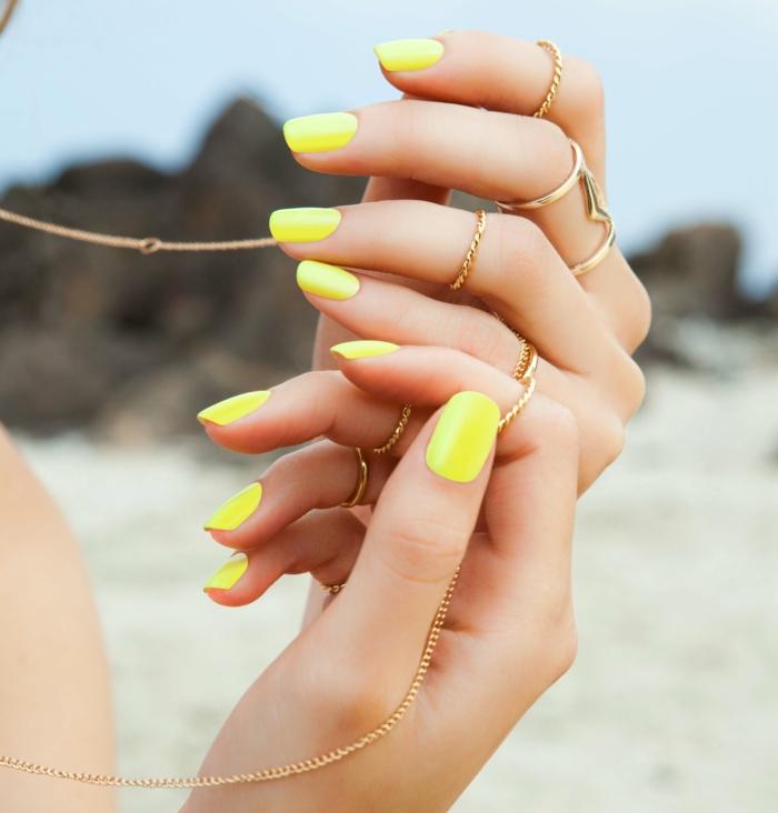nail art néon en jaune, chaîne doré, bague dorée, ongles ovales vernis jaune néon