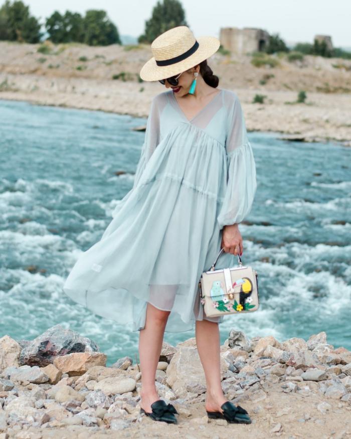 chapeau panama femme, robe légère bleu pâle, sac à main imprimé joyeux, boucles d'oreilles turquoises
