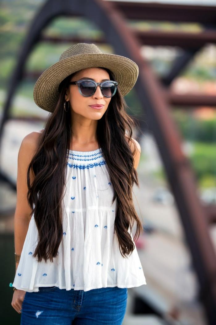 tunique avec broderies, jeans bleus, lunettes de soleil, chapeau beige en paille, chapeau d été pour femme