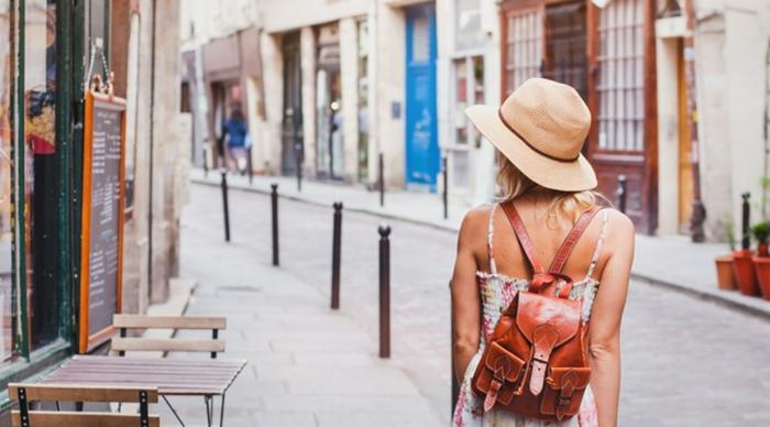 sac à dos en cuir, combinaison chic dos nu, chapeau fédora beige, café dans la rue, femme qui se promène