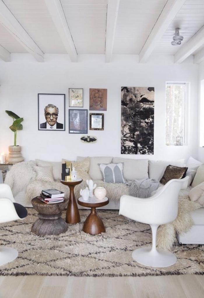 Salon bien aménagé, canapé blanche en angle avec coussins confortables et tables basses rondes style ethnique chic