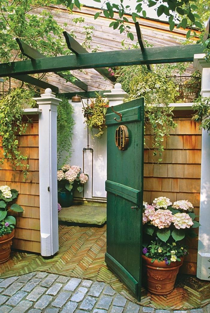 comment aménager une salle d'eau dans la cour arrière, exemple de salle de bain dans le jardin avec murs blancs et douche cuivre