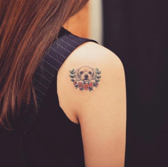 chien blanc aux fleurs, petit tatouage coloré, tatouage épaule femme en blanc, rouge et vert