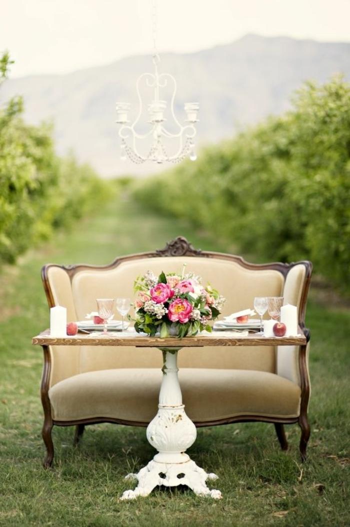 sofa baroque couleur crème, table en bois et blanc, chandelier, déco de fête shabby chic en plein air