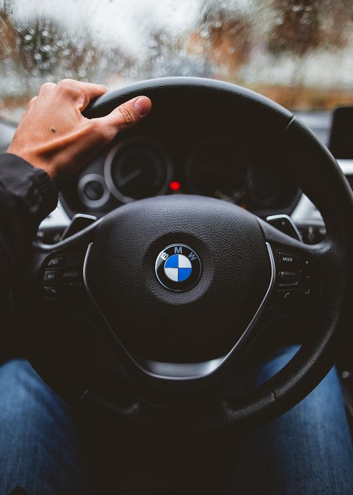 Photo dans un véhicule BMW, moteur à combustion, préférence pour les véhicules électriques de BMW, main qui tiens le volant