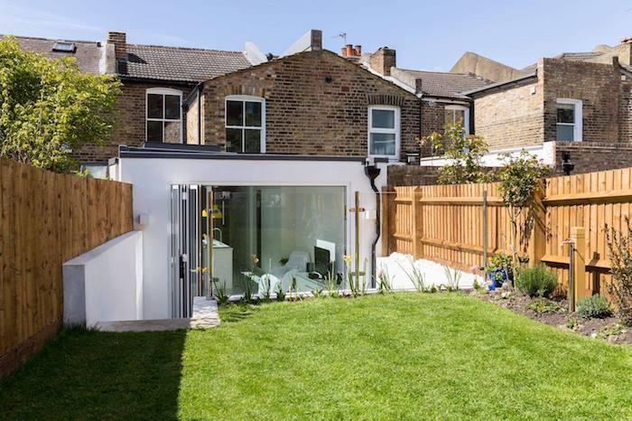 petit salon en blanc abrité par une extension contemporaine à coté d une maison de briques ancienne