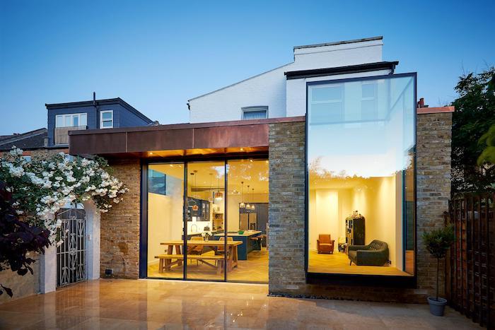 petit studio en extension d une maison contemporaine avec cuisine blanche, bleu et bois ouverte sur coin repas et salon minimaliste