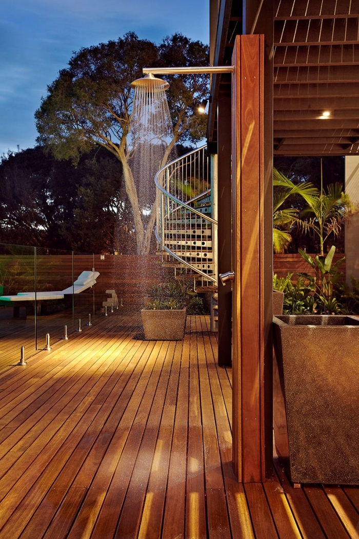 aménagement extérieur d'une maison moderne avec terrasse bois foncé, exemple de douche fixe sur colonne en bois marron