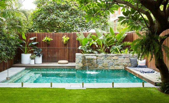 piscine avec escalier dans un jardin paysager magnifique, canisse bambou, muret en pierre naturelle, espace de détente, gazon