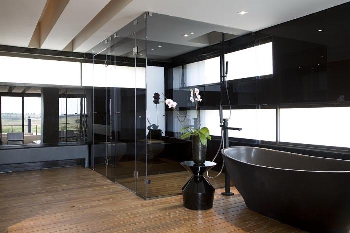 décoration luxueuse salle de bain aux murs noirs avec grandes fenêtres et plancher en bois, modèle de baignoire noire autoportante