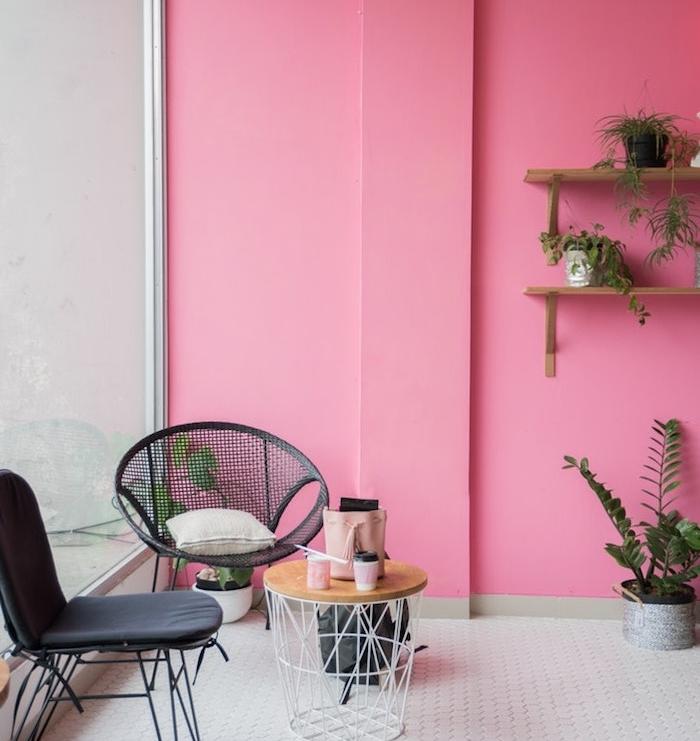 murs couleur rose, sol carrelage blanc, chaises noires et table poubelle, étagères bois décorées de plantes en petits pots verts