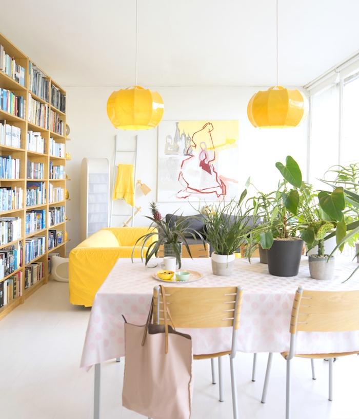 deco salon blanc aux accents jaunes et verts, pots de végétaux rangés sur une table za manger, bibliothèque bois, murs blancs