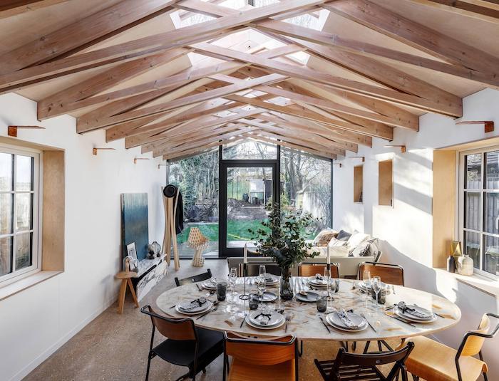 extension ossature bois originale avec des poutres apparentes croisées pour accueillir une salle à manger ouverte sur petit salon artistique