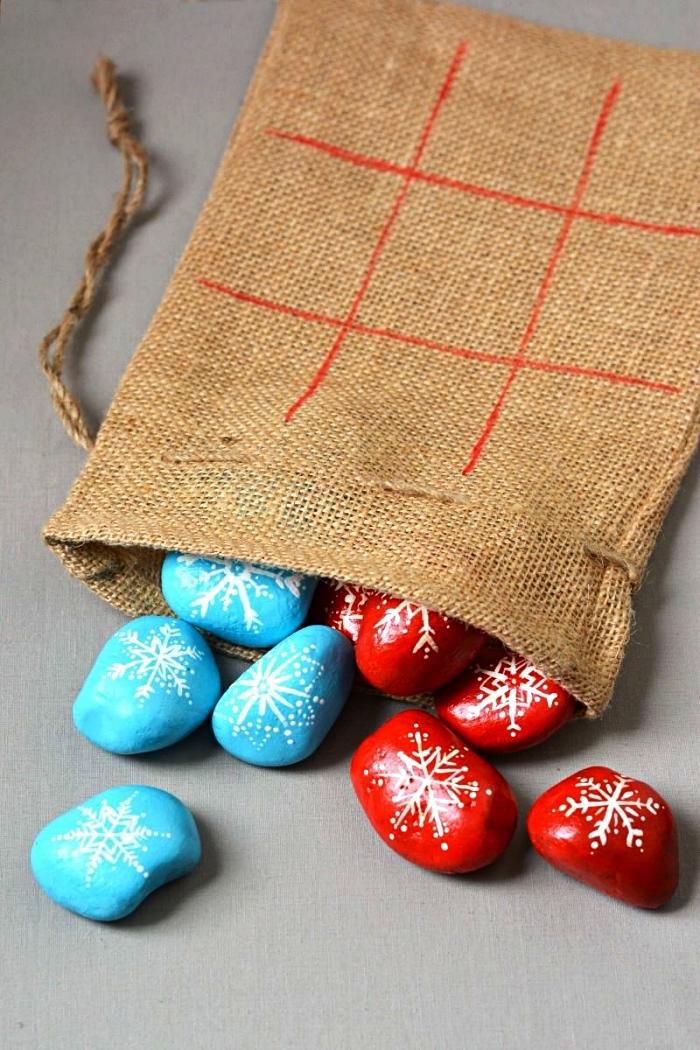 des galets pions en bleu et rouge pour le jeu de tic-tac-toe dans leur sac en toile de jute, fabriquer un jeu de morpion avec galets comme pions
